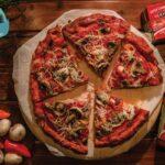 Ντοματένια βάση αφράτης πίτσας με μανιτάρια, πιπεριές και ελιές